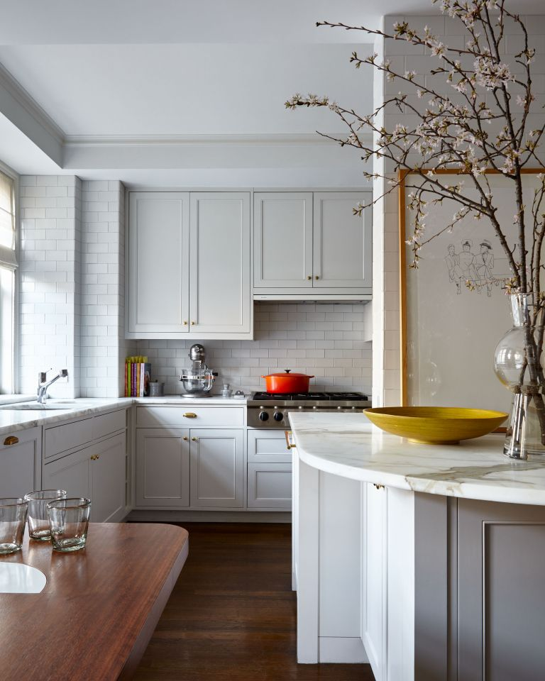 small kitchen with curvy marble countertop white units and dark wood floor