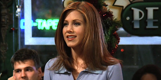 Jennifer Aniston as Rachel Green on Friends smiles as she talks in Central Perk.