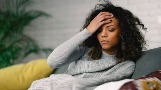 woman on couch holding head in pain