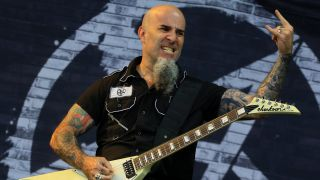 A photograph of Scott Ian on stage, giving the horns with a guitar, in 2015