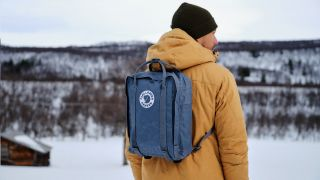 A man wearing a Fjallraven backpack looks at a snowy mountain