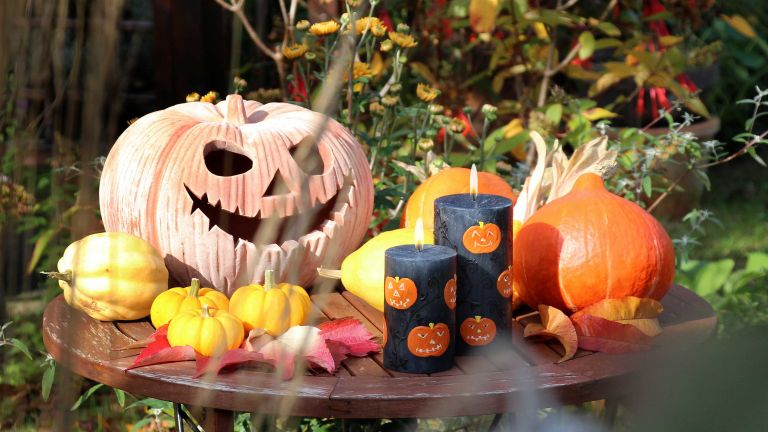 outdoor halloween decor ideas: pumpkins and candles in set-up from nobunto