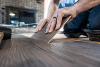 man installing engineered wood flooring