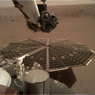 One of the two expansive solar arrays on NASA's InSight Mars lander dominates this view of the probe's Martian home, the plain of Elysium Planum, as seen on Dec. 4, 2018.