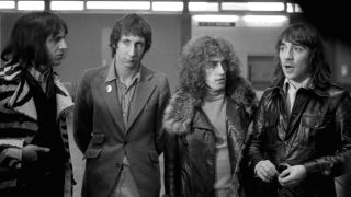 The Who standing in a row looking pensive.