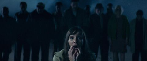 A woman screams in front of a shadowy group of people