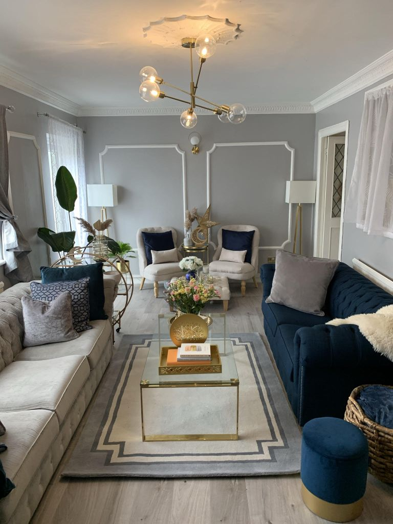 grey formal living room with brass chandelier