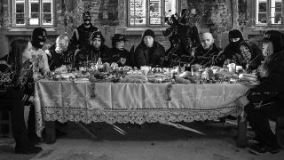 A press shot of King 810 sat at a last supper-esque table
