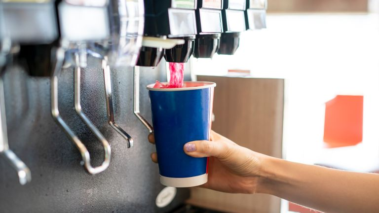 Person dispenses soda into a cup