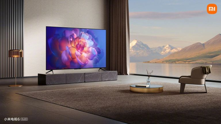 Xiaomi Mi TV 6 OLED in house, sitting on bench with large windows nearby showing a landscape view