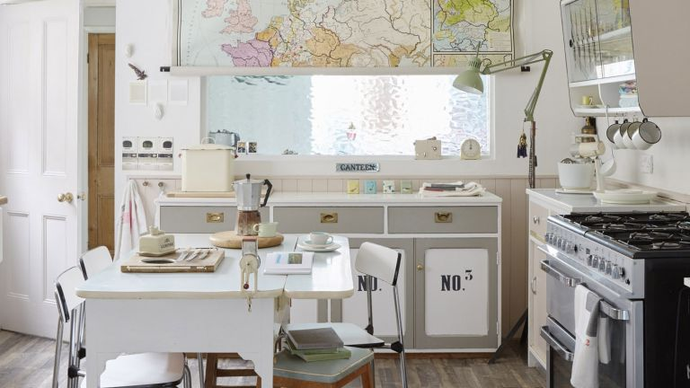 white kitchen with map print blind and white table and chairs and cooker