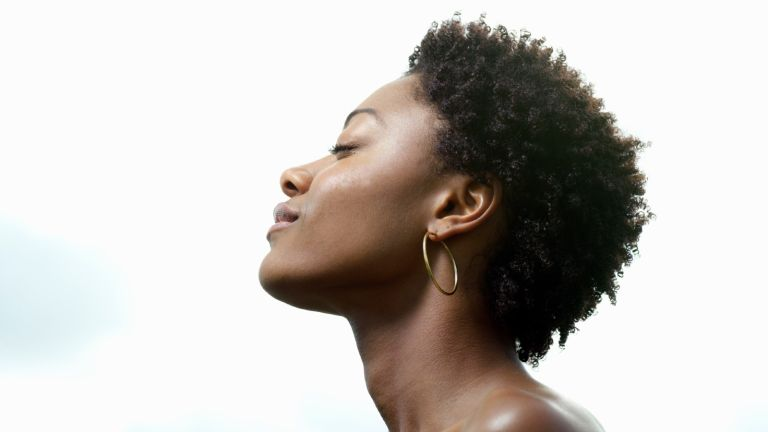 Young woman, eyes closed, low angle view, profile - stock photo