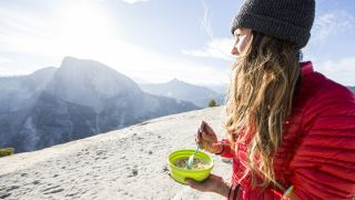 A woman eating a camping meal with Half Dome in the distance