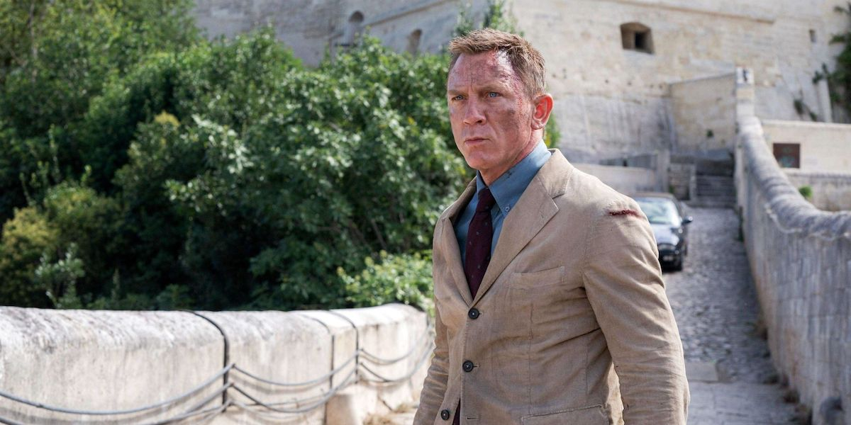 James Bond (Daniel Craig) stands on a stone bridge in 'No Time To Die'
