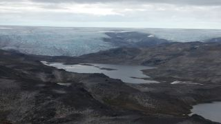 a landscape photo of an outcrop of Greenland's Isua supracrustal belt, shows valley with a pool of water in the center and a coastline and ocean beyond