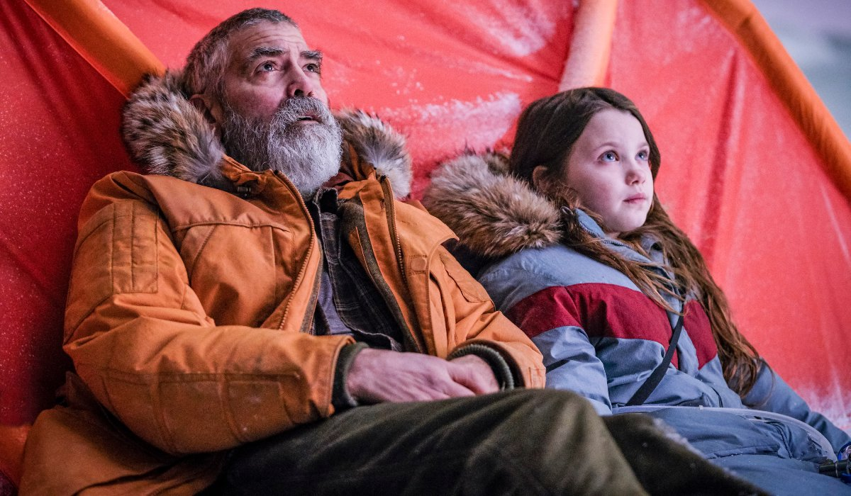 The Midnight Sky George Clooney and Caoilinn Springall sitting in front of their tent