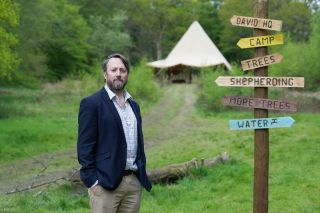 Outsiders: David Mitchell stands in the woods next to a wooden signpost with branches pointing to 'David HQ', 'Camp', 'Trees', 'Shepherding', 'More Trees' and 'Water', with a tent in the background