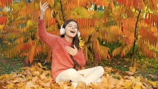 Girl listening and singing to music with headphones on in Autumn season