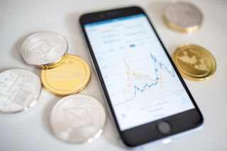 illustration of the litecoin, ripple and ethereum cryptocurrency 'altcoins' sit arranged for a photograph beside a smartphone displaying the current price chart for ethereum