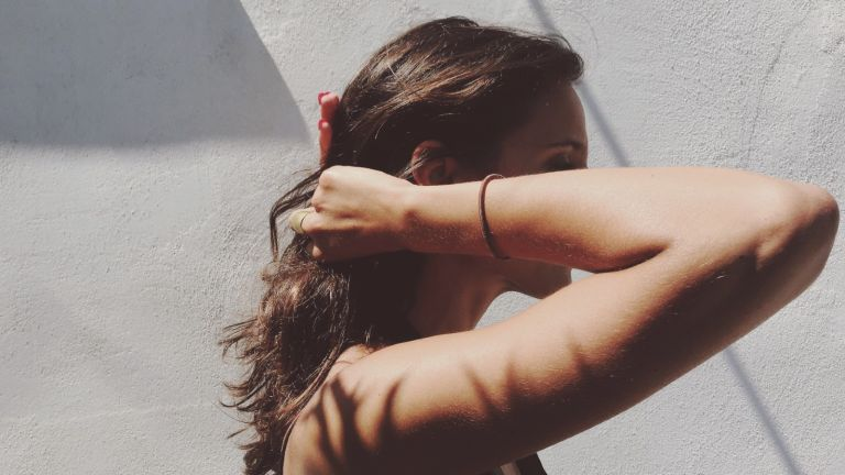 Side View Of Woman Tying Hair Into Ponytail - stock photo