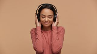 a girl in a pink jumper holding he rhands over her headphones with her eyes closed