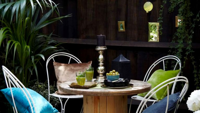 Black painted fence with dining set and green plants
