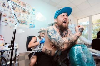 Man in pain at tattoo shop