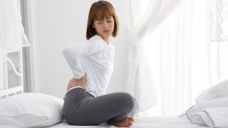 A woman sits on a mattress holding a hand to her lower back