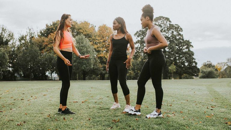 A group of three women are pictured in a luscious green park in their best workout and exercise gear with crop tops and leggings