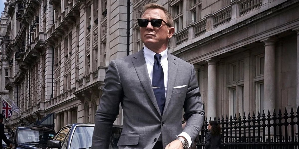 No Time To Die Daniel Craig, in sunglasses, walks down the street wearing a grey suit