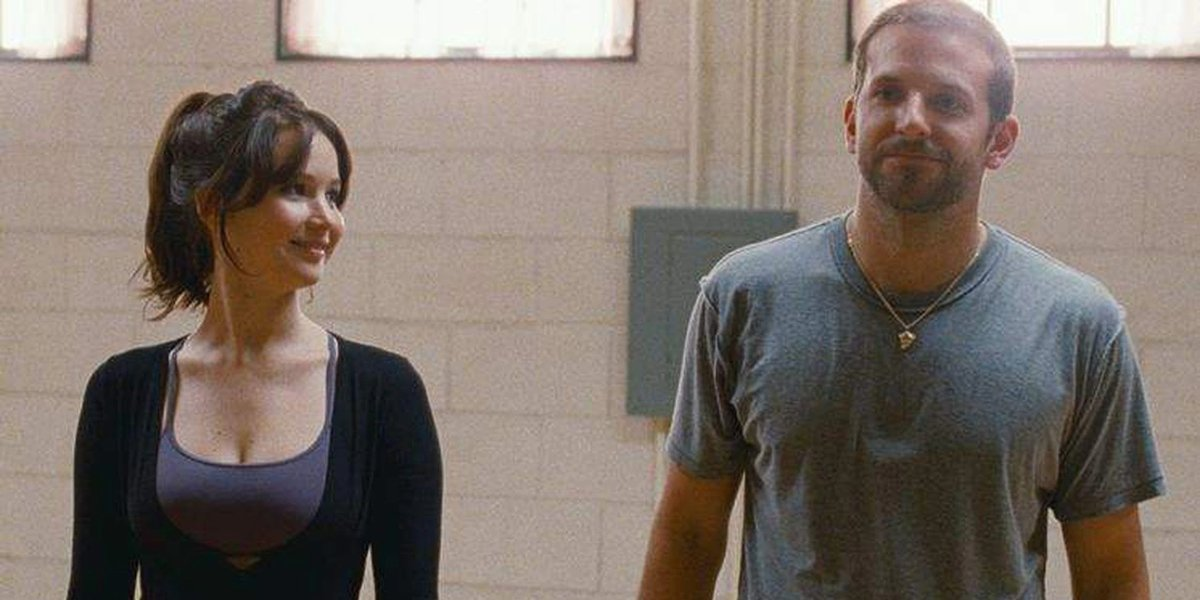 Jennifer Lawrence and Bradley Cooper smile during dance practice in Silver Linings Playbook.