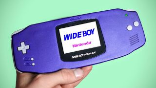 A Modded version of the gameboy advance held in a hand on a mint green background