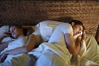 A couple in bed with the man struggling with a sleep disorder.
