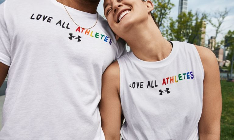 Models wearing a t-shirt with the slogan 'love all athletes', part of the Under Armour Pride Collection