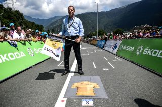 Tour de France director Christian Prudhomme holds the starting flag for the grid-start of stage 17