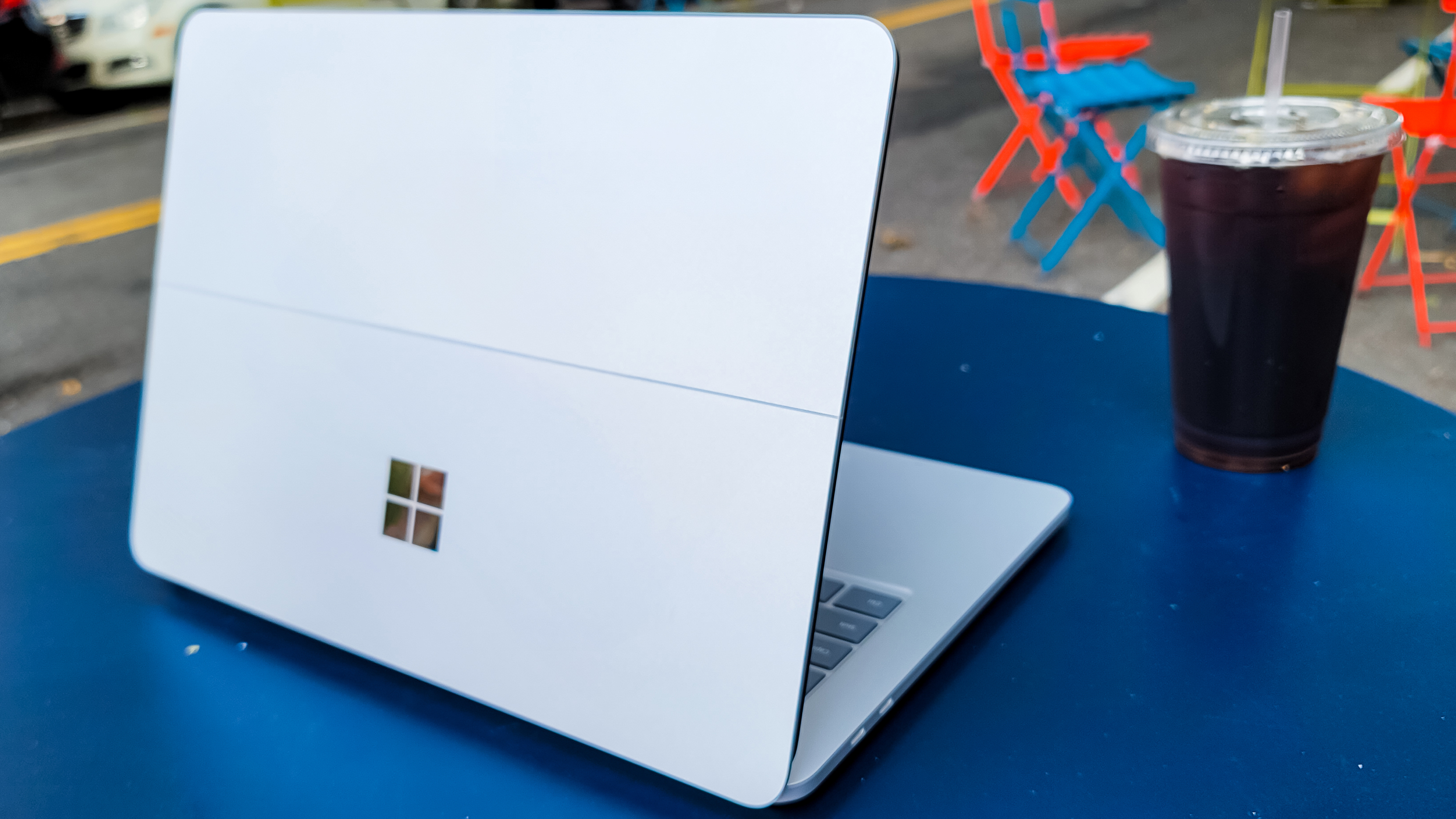 Surface Laptop Studio from behind, on a blue table next to iced coffee