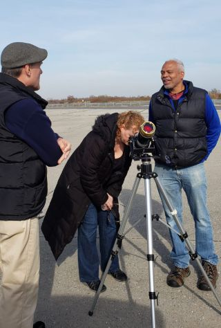 Former journalist Martin Evans (right) chats with two fellow guests of the Amateur Astronomers Association (AAA) gathering on Monday, Nov. 11, 2019, in Floyd Bennett Field, New York. Peering through the Orion EZ Finder II telescope is a mother who brought her children to the viewing event; standing to the left is amateur astronomer Stephen Lieber.