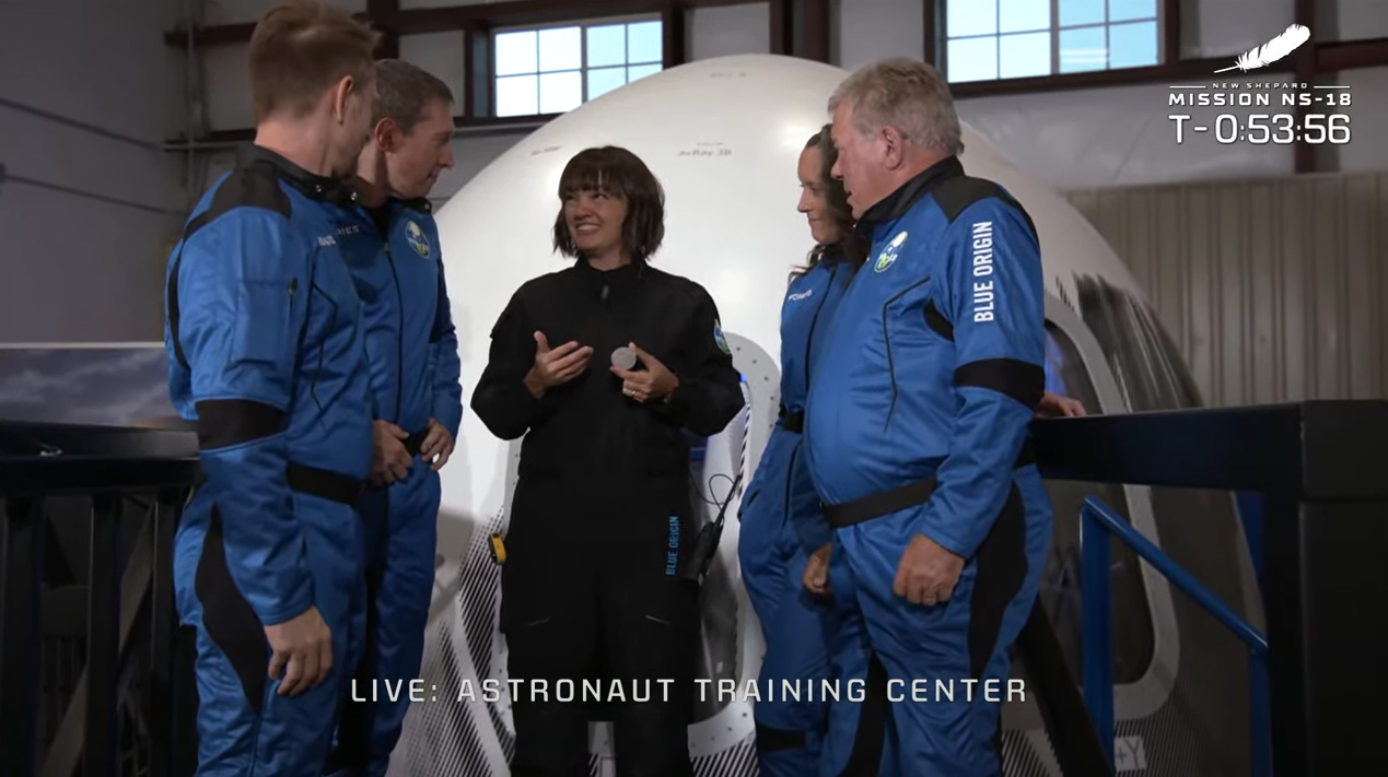 Blue Origin's Crew Member Seven Sarah Knights presents William Shatner and his three crewmates their commemorative challenge coins to signify the completion of their training for the NS-18 launch..