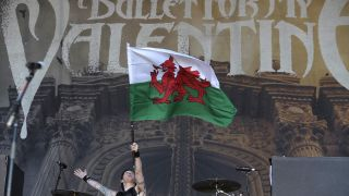 Drummer Moose from Bullet For My Valentine holding up the Welsh flag onstage.
