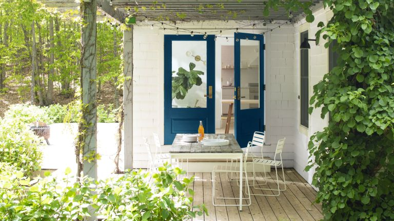 An example of how to make a small garden look bigger with a covered decking area beside a white brick house with blue doors.