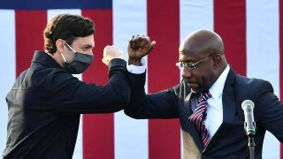 Democratic Senate candidates Jon Ossoff and Raphael Warnock bump elbows at a campaign rally.