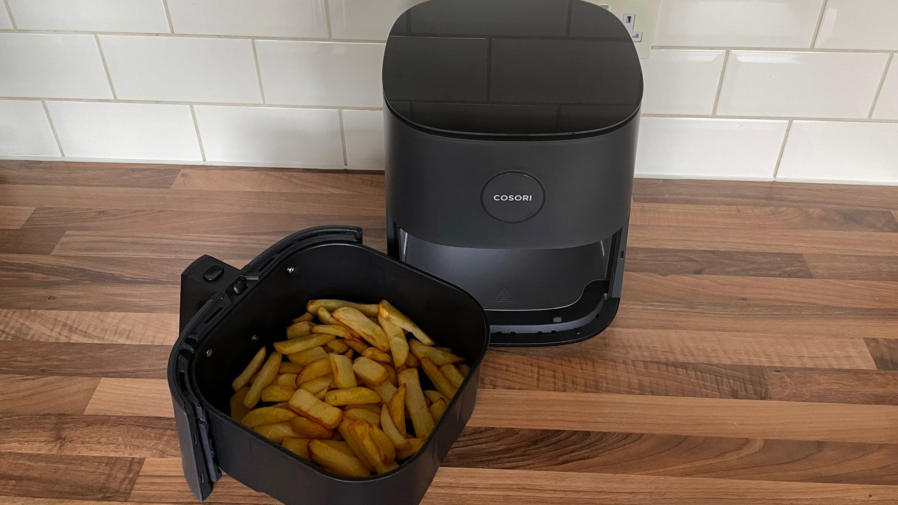The Cosori Pro LE Air Fryer L501 with the frying basket containing fries removed