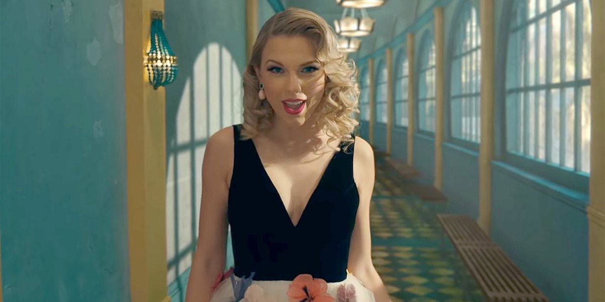 Taylor Swift walking through a blue hallway in the ME! music video for Lover album