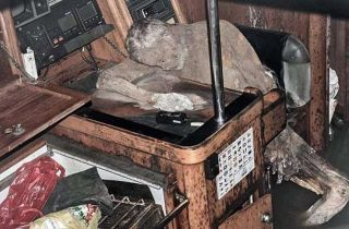 A mummified sailor seated at a desk.