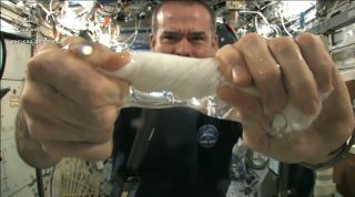 "Canadian astronaut Chris Hadfield shows just what happens to a wet washcloth in space when you wring it out without the help of gravity. The result: a ""tube"" of water."