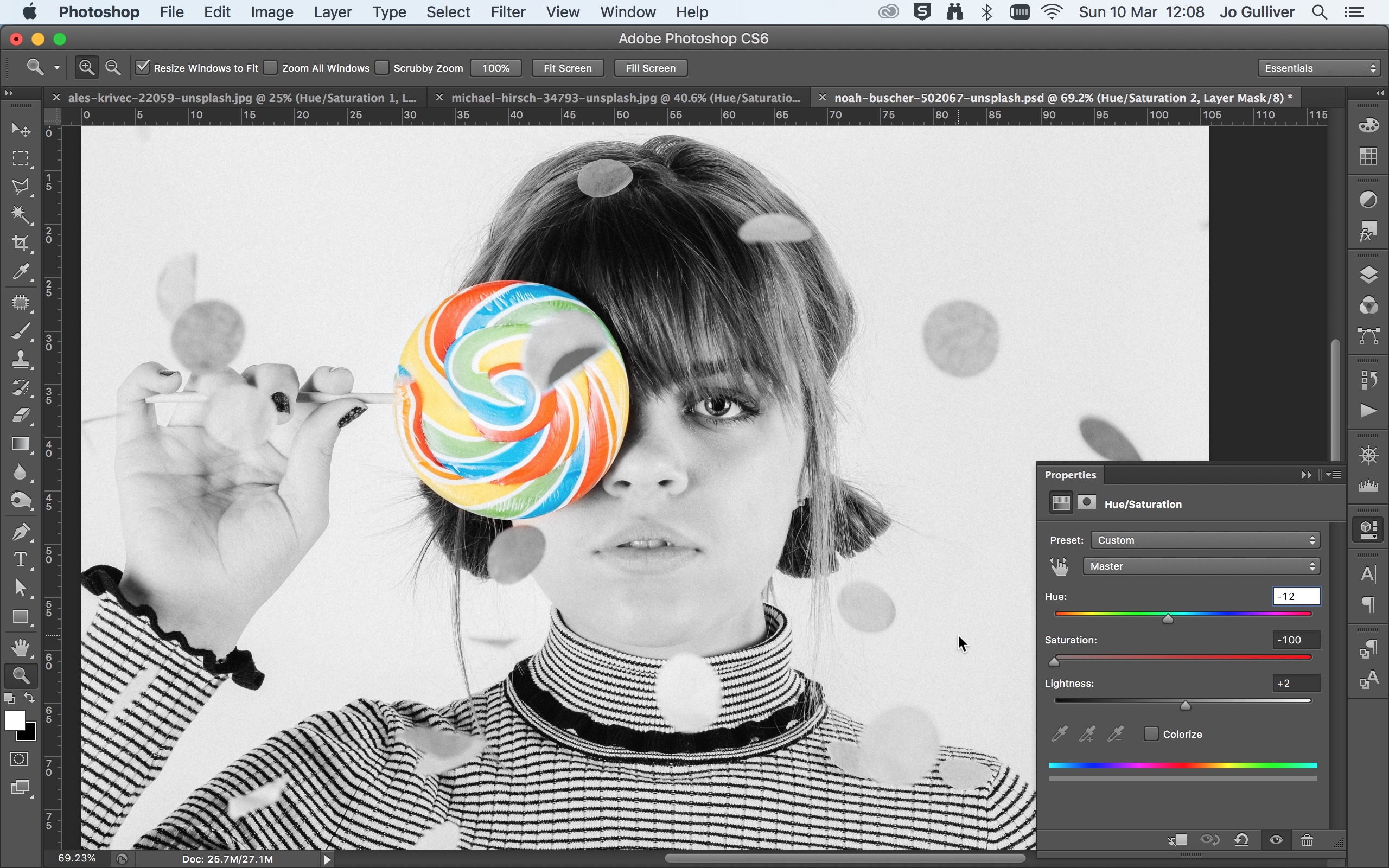 Black and white photo of a woman holding a colour lollypop in front of her right eye