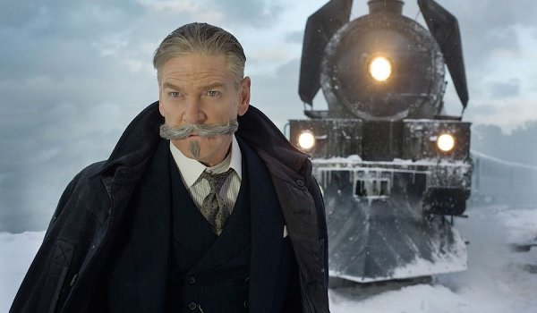 Murder on the Orient Express Hercule Poirot posing in front of the train