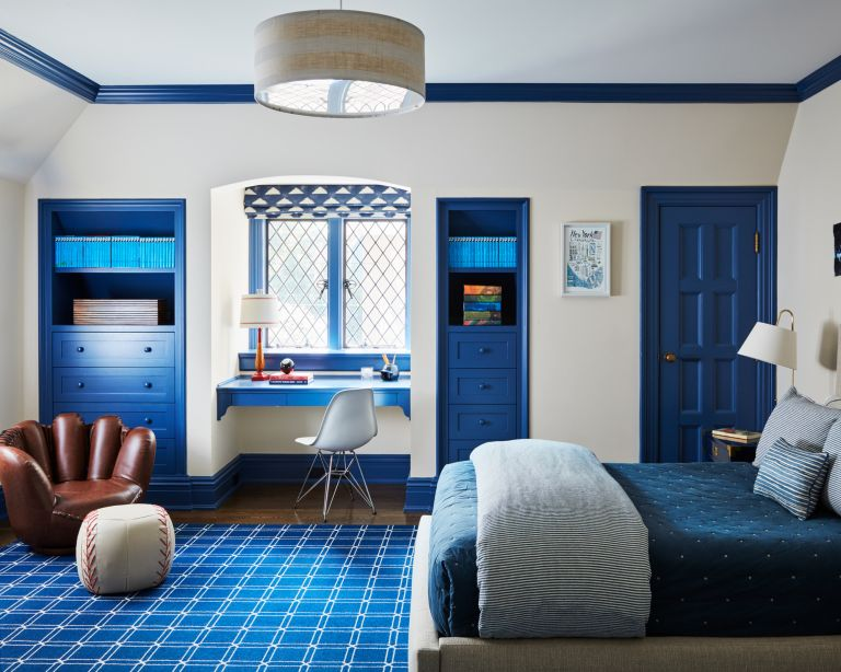 Bedroom ideas for boys with white walls, blue painted accents, a built-in blue desk in the alcove window and a chair shaped like a baseball mit