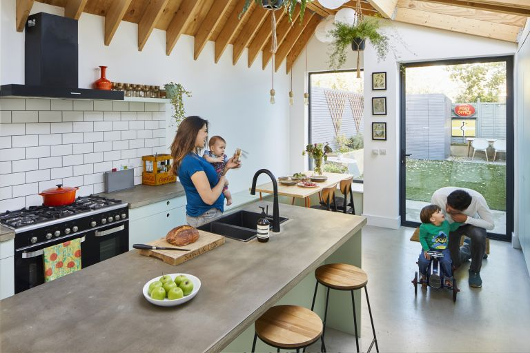 A kitchen extension with large pivot door and picture window, concrete-effect worktops and floor, and exposed beams in the pitched extension roof