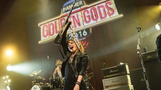 A photograph of Lzzy Hale raising her guitar onstage at the Golden God Awards